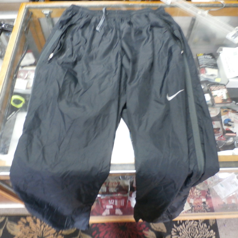 Nike Running pants with zip pockets black size medium 100% nylon #25379<br /> Rating: (see below) 3- Good Condition<br /> Team: n/a<br /> Player: n/a<br /> Brand: Nike<br /> Size: Men&#039;s Medium-  (Measured Flat: Waist 13&quot;; Length 40&quot;; Inseam 31&quot;)<br /> Measured flat: hip to hip; hip to hem; and groin to hem<br /> Color: black<br /> Style: zip pockets; elastic waistband w/ drawstring<br /> Material: 100% nylon<br /> Condition: 3- Good Condition; wrinkled; some pilling and fuzz; material is stretched and worn from wearing and washing; some discoloration and fading; gray marks on right leg near pocket; no rips or tears (see photos)<br /> Item #: 25379<br /> Shipping: FREE
