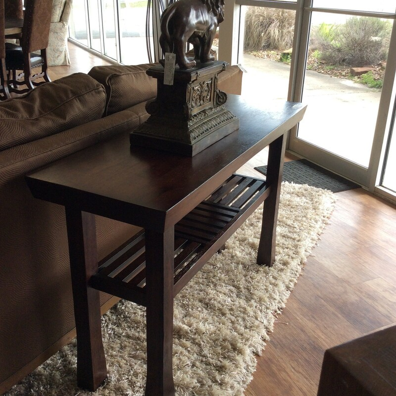 This sofa table originally from World Market feaures a rich, dark wood finish and a little distressing for added character. It also includes a lower tier for displaying items or could be used as a bookshelf. Good condition.