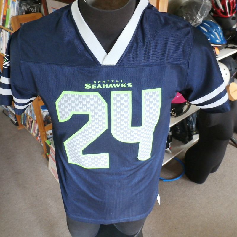 Seattle Seahawks Marshawn Lynch YOUTH jersey size XL (16/18) polyester #26039<br /> Rating: (see below) 4- Fair Condition<br /> Team: Seattle Seahawks<br /> Player: Marshawn Lynch<br /> Brand: NFL<br /> Size: YOUTH XLarge (16/18) - (Measured Flat: chest 19&quot;, length 27&quot;)<br /> Color: blue<br /> Style: short sleeve; screen printed<br /> Material: 100% polyester<br /> Condition: 4- Fair Condition; wrinkled; material is stretched and worn from wearing and washing; some pilling and fuzz; some fading and discoloration; no rips or tears; no stains; screen printing on front is peeling off; threads coming loose on right sleeve (see photos)<br /> Item #: 26039<br /> Shipping: FREE