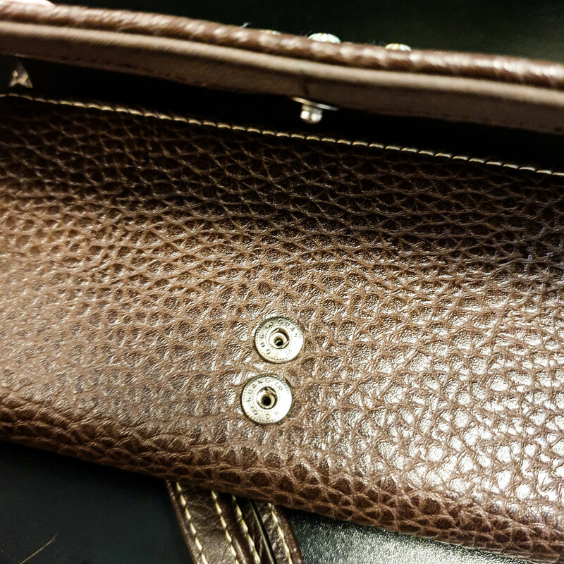 Beautiful Shyanne Wallet.<br /> - Dark brown leather<br /> - Studs details<br /> - Cowhide detail<br /> - Adjustable button closure<br /> - Back zip pocket<br /> - Adjustable wristlet<br /> - Interior features: one zip pocket, eleven card slips, four slip pockets and three ID windows<br /> - W: 7.5 in. H: 4 in. D: 1.25 in.<br /> <br /> * Please note that these measurements and pictures are for reference only and may vary slightly from the original.