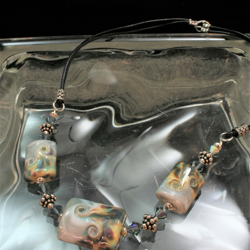 From the Mystic Swirls collection of Gladmist Glass Design. Hand torched glass bead necklace with Sterling Silver and Swarovski crystals. Necklace is finished with black leather and easy but secure hook and eye closure. Finished length is 19 inches.