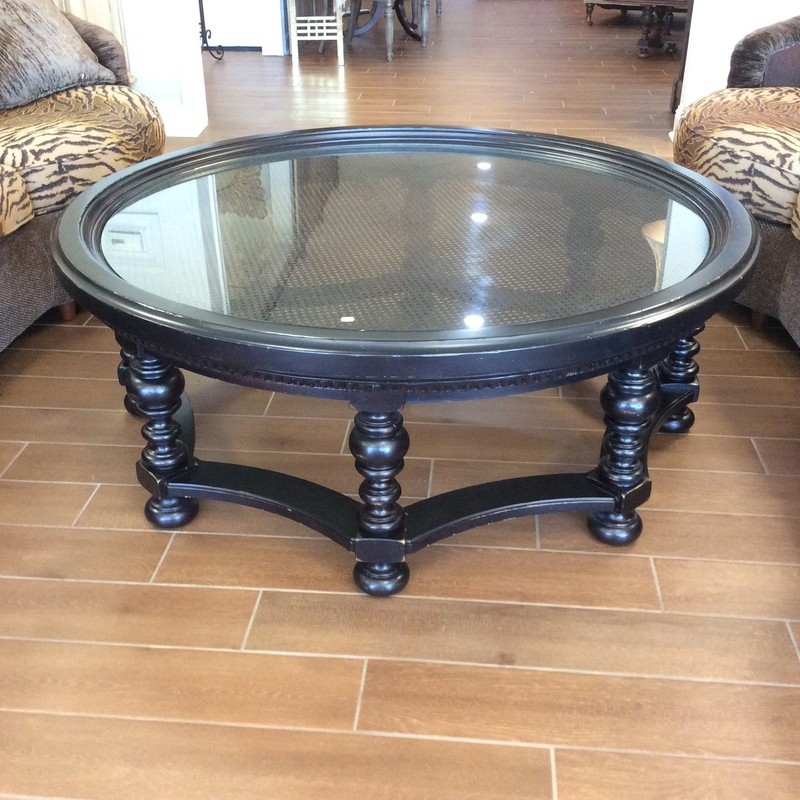 This is a pretty large coffee table. It is solid wood with a matte black finish and has a caned top that is covered by a glass topper. Really pretty!