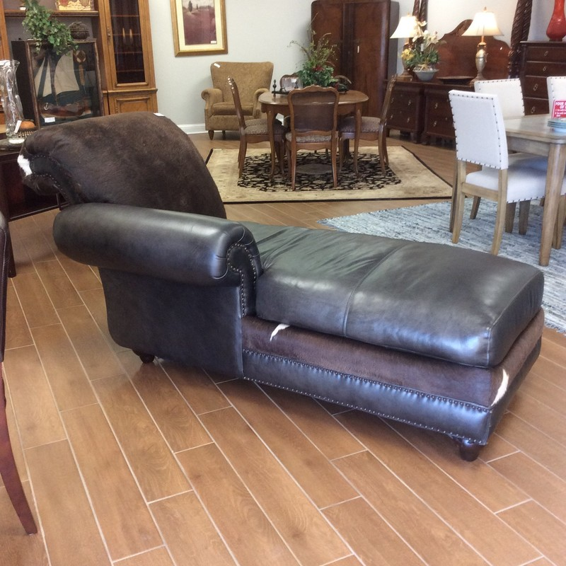 This is a very handsome chaise lounge. It is over 6 feet long and features both leather ans cowhide upholstery. It has nailhead accents, as well.