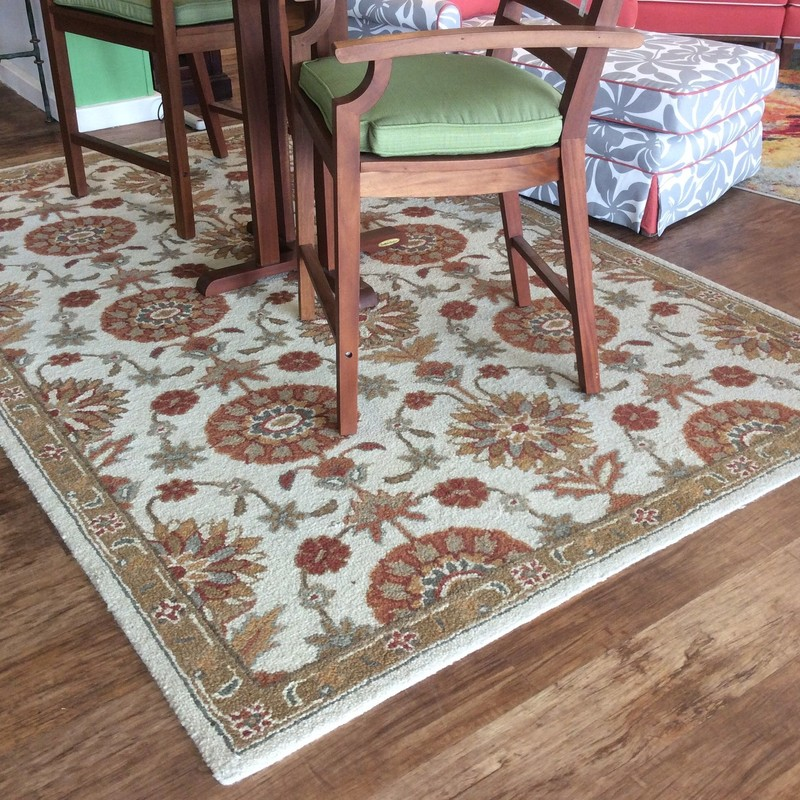 This is a very nice looped wool rug! Handcrafted by village weavers in India it features a lovely floral pattern in soft, muted colors - cream, rust, orange and green/gray. It measures 6' x 9'.