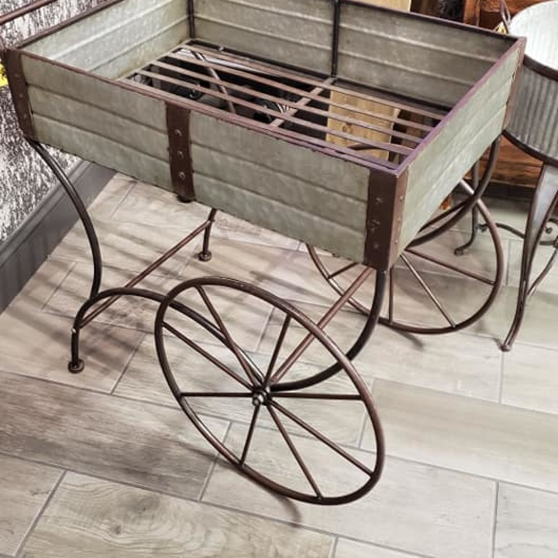Galvanized Planter Carts<br /> Very unique galvanized metal plant carts. They have large metal vintage style wheels and a curved handle. Great addition to any home or garden. They measure 36&quot; long x 21&quot; deep x 30&quot; tall. Buzz on in to see them today!