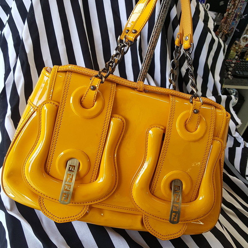 Beautiful Bright yellow Patent leather Fendi tote. With brushed antique gold chain handles. Button clasp front with metal Fendi emblem detail on front. Good condition! Some scratches on back, but very light wear. Otherwise great bag!! Retail: $1,950