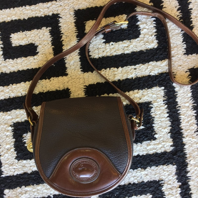 LIKE NEW, Dooney and Bourke crossbody. Classic black leather with smooth, brown leather detailing. Adjustable strap and exterior pockets.
