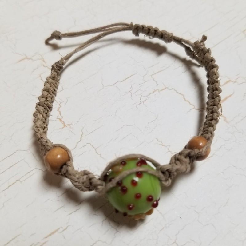 Hemp Bracelet with green/red bead. Handcrafted and adjustable.