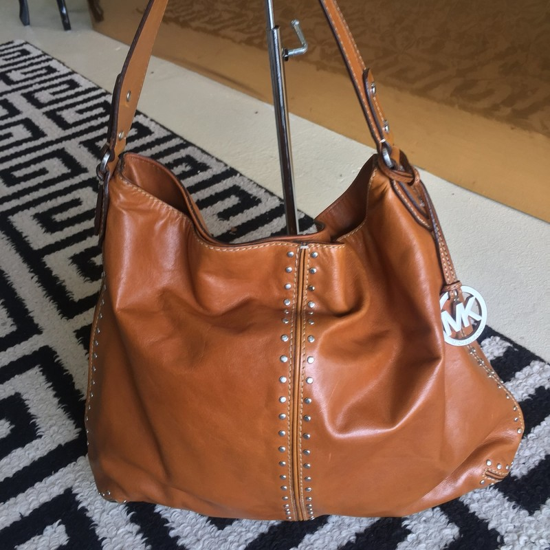 Michael Kors hobo bag. Large, with brown exterior with tan canvas interior. Good condition, few scrapes and discoloration due to wear. Silver studs and silver hardware.