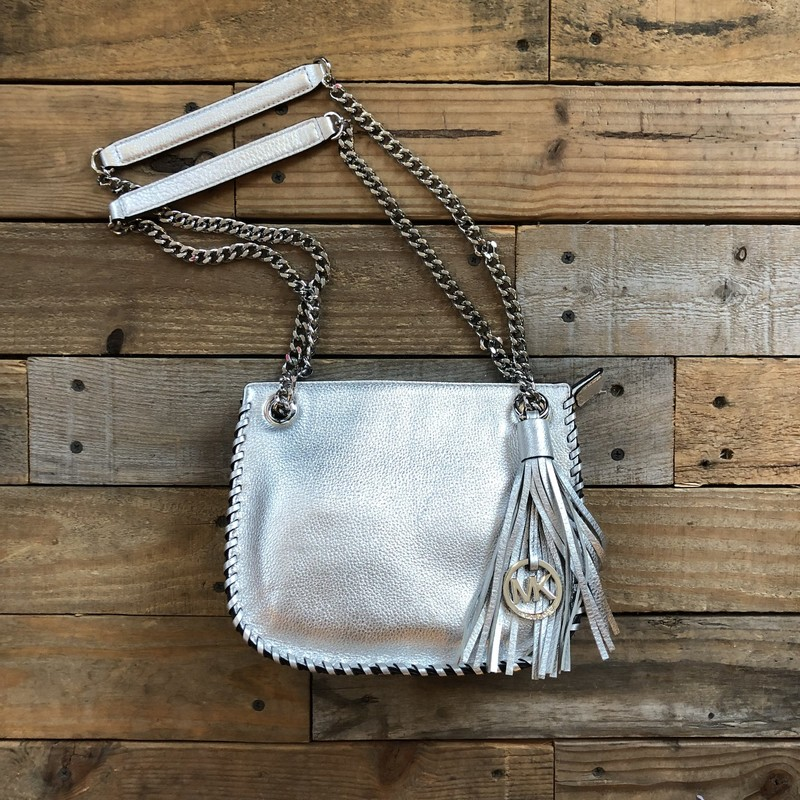 "Michael Kors Crossbody Bag<br /> Color: Silver<br /> Size: 9""L x 7""D x 2.75""W (13"" *double strap or 25"" *single strap shoulder length)<br /> Material: Leather<br /> <br /> Features:<br /> -Chain link straps (double or single use)<br /> -Interior zippered pocket<br /> -Hidden exterior magnetic close pocket<br /> -Woven exterior seams<br /> -Zippered closure<br /> -Removable leather tassel with MK logo"
