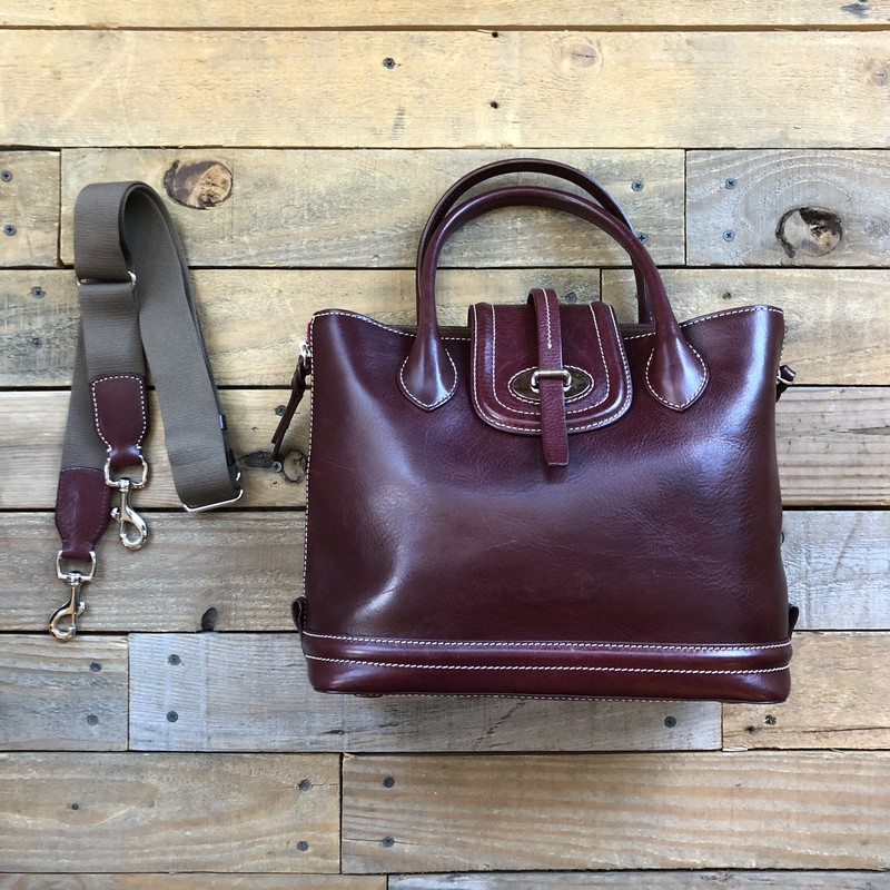 "Dooney & Bourke Leather Handbag<br /> Color: Dark Red-Brown<br /> Size: 12""L x 10""D x 5""W<br /> Material: 100% Leather<br /> <br /> Features:<br /> -Leather flap closure<br />  -5"" drop handle<br /> -Zippered sides for expansion<br /> -Removable & adjustable fabric & leather strap<br /> -All leather interior<br /> -Interior zippered pocket<br /> -Two interior pockets<br /> -Interior key hook<br /> -Includes dust bag"