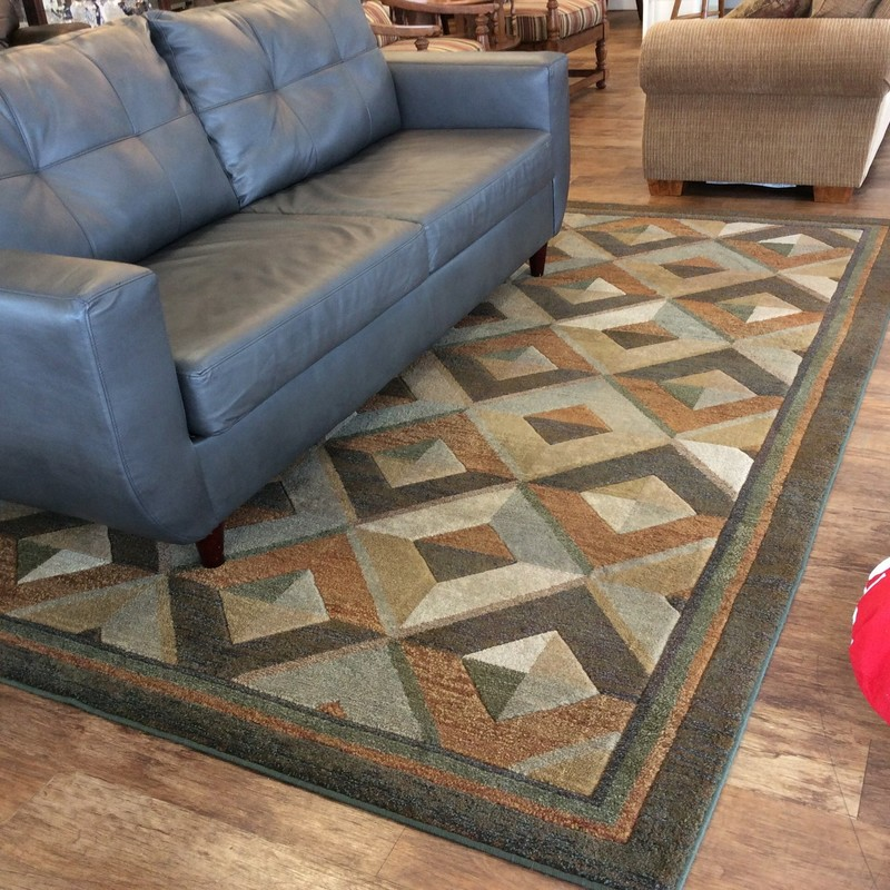 This is a handsome rug. It features a geometric pattern that includes browns, grays, blues and greens. It is 100% polypropelene and measures 8 feet by 10 feet.