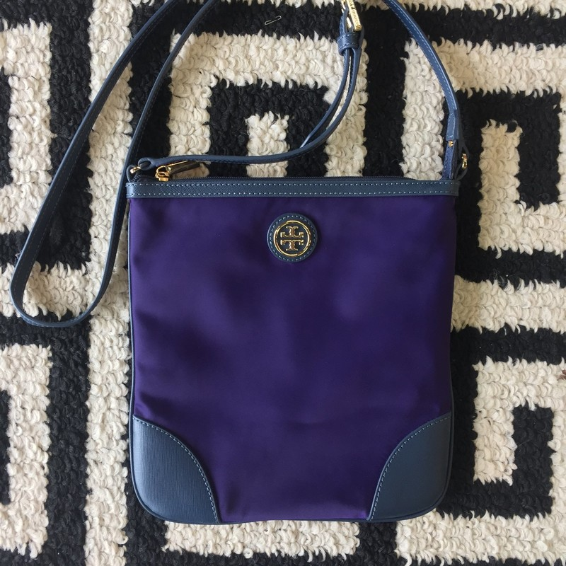 LIKE NEW Tory Burch nylon and leather crossbody. Purple-blue nylon with blue leather and gold hardware. Clean, no stains or holes. Adjustable strap. Retail approx: $198