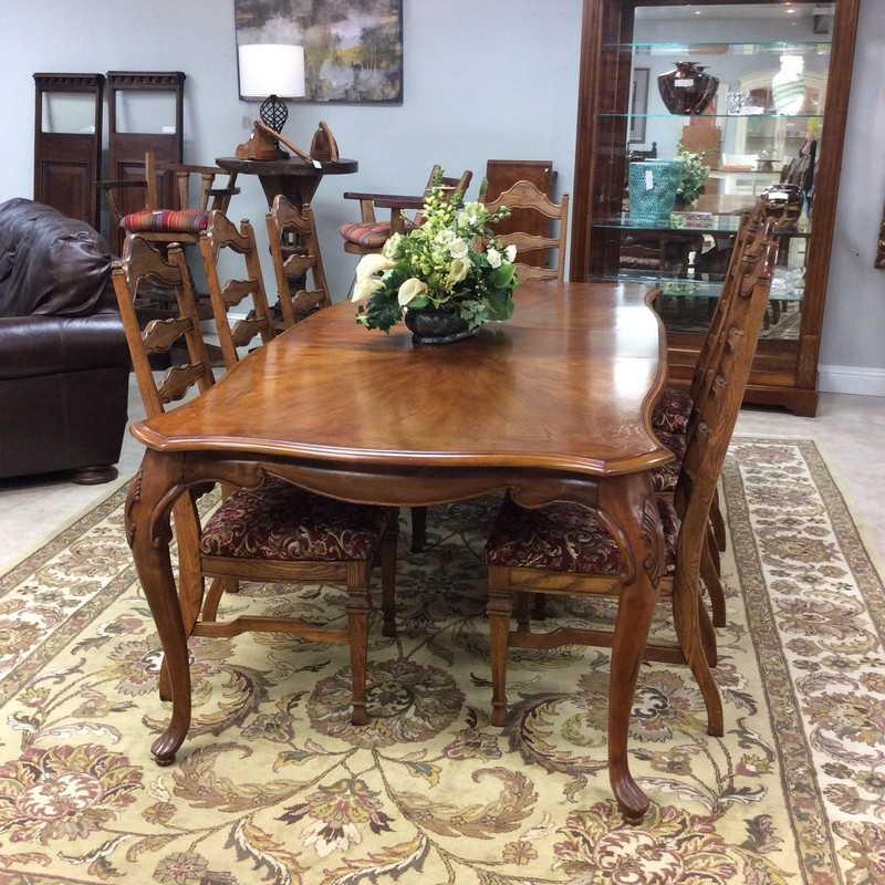 This dining room set by Kent is one of many dining room sets we've taken in this week. So, if you're in the market you need to come by! This one is very large and could accomodate quite a  gathering. Constructed of oak it comes with 8 chairs and 2 leaves. The chairs have a ladderback and have been upholstered in a bold red, green and cream floral print. Good condition.