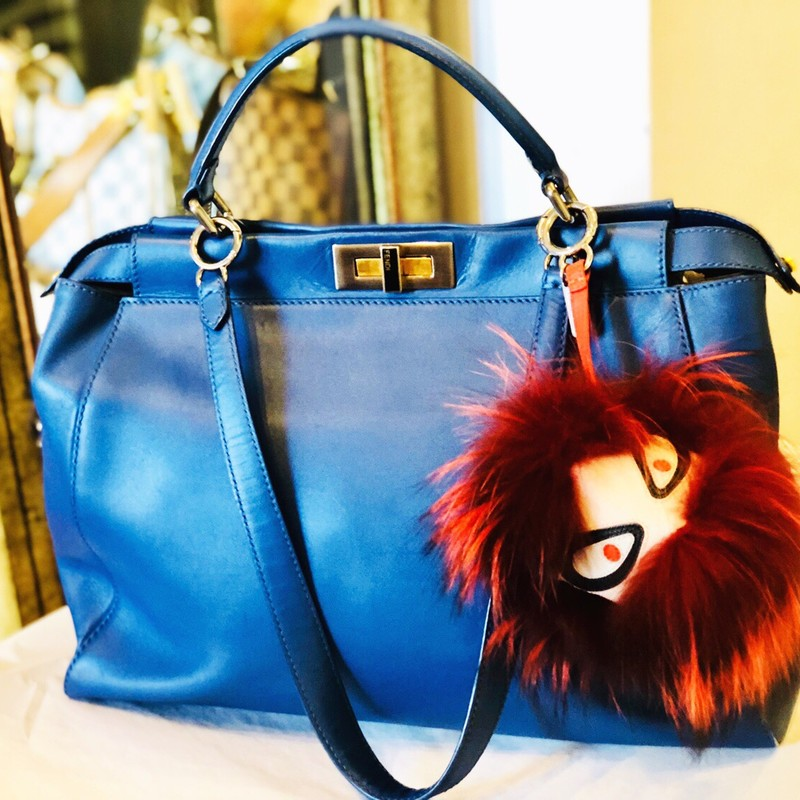 Retail is over $4700! Blue leather Fendi Large Peekaboo tote with multi-tonal hardware,  leather trim, optional flat shoulder strap, single flat top handle, peg-in-hole adornments at sides, protective feet at base, dual interior compartments, blue suede lining, dual pockets at interior wall; one with zip closure and turn-lock closures at top. Includes Monster charm adornment.<br /> Shoulder Strap Drop: 21&quot;<br /> Handle Drop: 5&quot;<br /> Height: 12&quot;<br /> Width: 17&quot;<br /> Depth: 7&quot;<br />  Condition is Very Good. Shape has relaxed due to wear; minor scuffing and scratches throughout leather; minor surface scratches at hardware. Includes Monster keychain (attached) a sepeartae $300 plus value!!