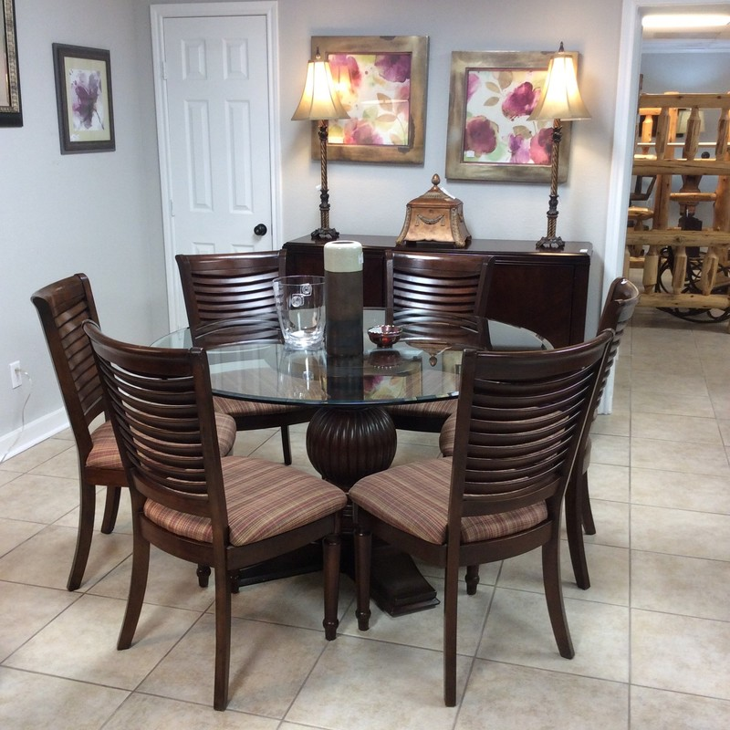 This dining room set is glass - topped with a dramatic pedestal base and includes 6 chairs uphostered in a brow, tan and red plaid.