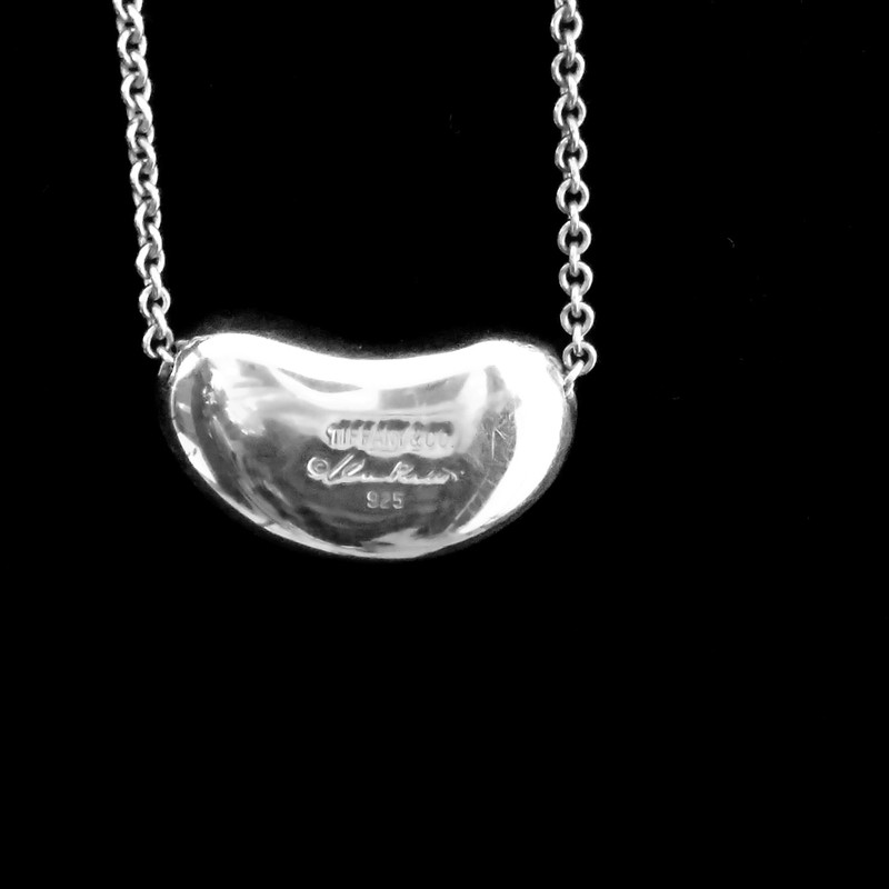 "TIFFANY & CO. SILVER<br /> 19"" SILVER NECKLACE &<br /> SILVER BEAN PENDANT<br /> DESIGNER ELSA PERETTI®<br /> THE BEAN REPRESENTS THE ORIGIN<br /> OF ALL THINGS<br /> NEW $300"