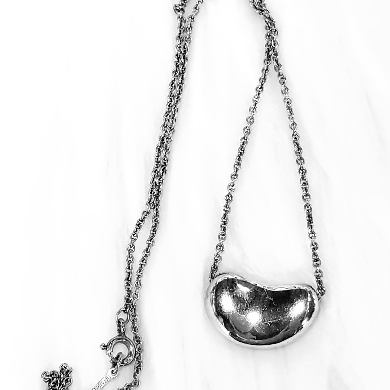TIFFANY &amp; CO. SILVER<br /> 19&quot; SILVER NECKLACE &amp;<br /> SILVER BEAN PENDANT<br /> DESIGNER ELSA PERETTI®<br /> THE BEAN REPRESENTS THE ORIGIN<br /> OF ALL THINGS<br /> NEW $300