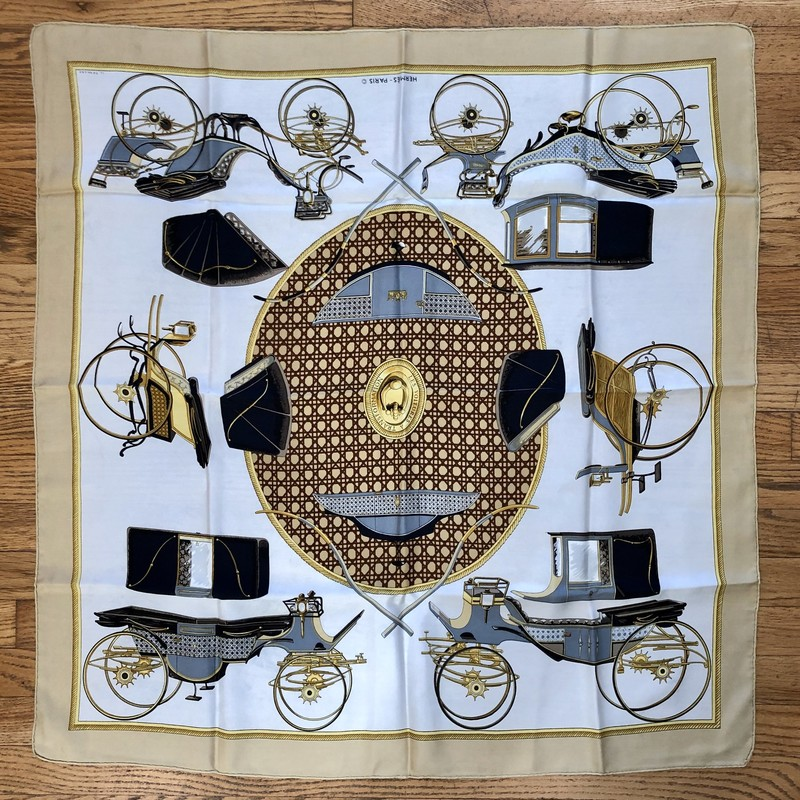 A lovely, pre-loved Vintage HERMES Scarf<br /> Design: Les Voitures A Transformation<br /> Colors: Browns, Black, Gray, Cream, Gold<br /> Size: 45&quot; x 45&quot; (approximate dimensions, which will vary due to wear and cleaning)<br /> &quot;Transformation&quot; or &quot;Carriage Changes&quot; by the artist Francoise de la Perriere that depicts &quot;transforming&quot; carriages, where we see various carriages from the mid to late 19th century and their interchangeable hard tops and soft hoods. This popular design was issued in 1980, 1990-02, 2000, and 2008, and as a 70cm x 70cm scarf in 2013.<br /> Condition: No tears or stains. There are smudges which appear as a very light gray, most likely transferring dye from the black areas.<br /> This is a pre-loved scarf, sold in &quot;AS IS&quot; condition. Please see the last pictures for examples of the light gray smudging.