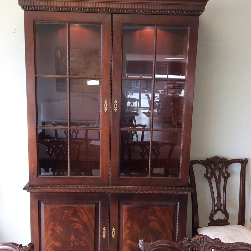 This is such a pretty display cabinet! It was made by HURTWITZ MINTZ and features solid wood construction, a nice mahogany finish and a lower 2-door cupboard with an adjustable shelf on each side. The upper cabinet has 2 adjustable wood/glass shelves, as well.