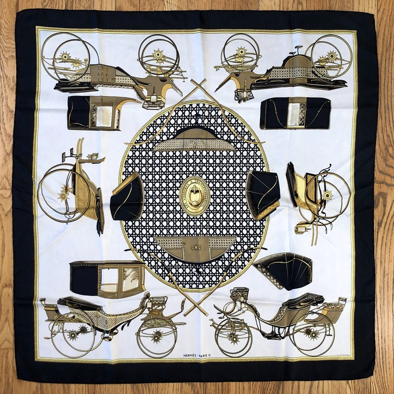 A lovely, pre-loved Vintage HERMES Scarf<br /> Design: Les Voitures A Transformation<br /> Colors: Black, Browns, Cream, Gold<br /> Size: 45&quot; x 45&quot; (approximate dimensions, which will vary due to wear and cleaning)<br /> &quot;Transformation&quot; or &quot;Carriage Changes&quot; by the artist Francoise de la Perriere that depicts &quot;transforming&quot; carriages, where we see various carriages from the mid to late 19th century and their interchangeable hard tops and soft hoods. This popular design was issued in 1980, 1990-02, 2000, and 2008, and as a 70cm x 70cm scarf in 2013.<br /> Condition: No tears, one stain. There are smudges which appear as light gray, most likely transferring dye from the black areas. One very light pink smudge, most likely transferred from another Hermes Scarf.<br /> This is a pre-loved scarf, sold in &quot;AS IS&quot; condition. Please see the last pictures for examples of the light gray/pink smudging, and the one light brown stain.