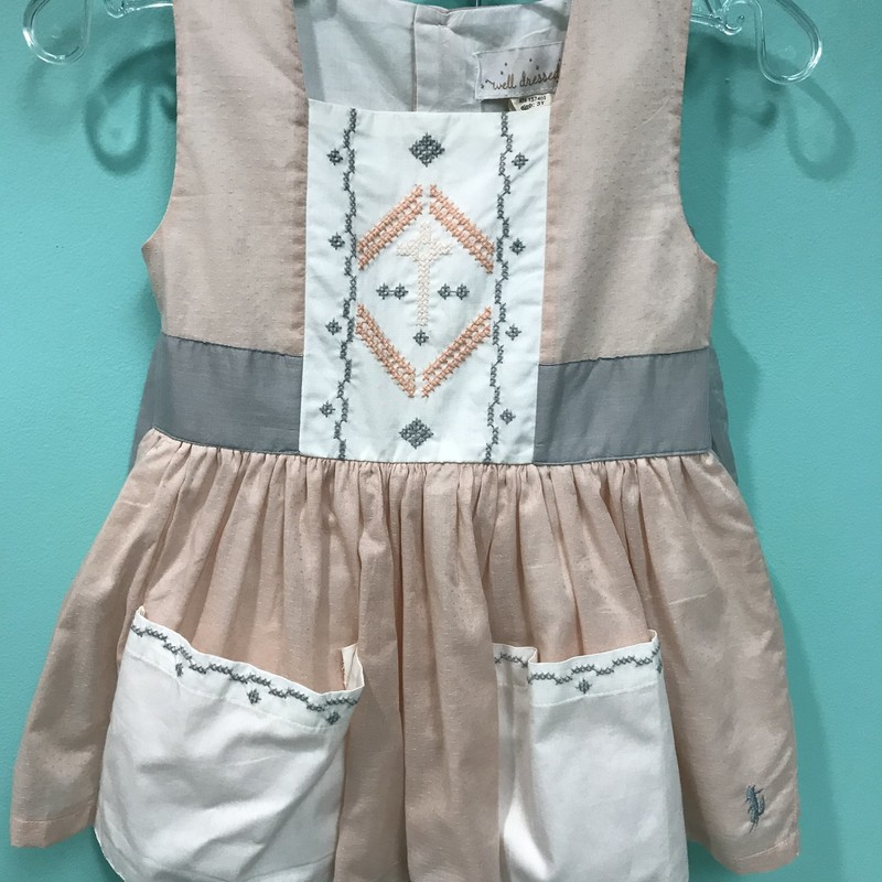 Well Dressed Wolf Brand<br /> Peach Sunday Cross Stitch Outfit<br /> New With Tags<br /> Peach, Cream and Grey Colors<br /> Grey Shorts<br /> Two Pockets on the front<br /> Ties around the back<br /> Toddler Size 2