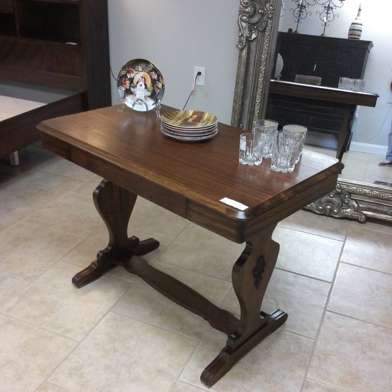 This is a sweet antique entryway table! It features simple, clean lines and a rather spacious drawer with dovetail jointing. Each side has a metal fleur-di-lis medallion attached. It's in very good condition for an oldie.