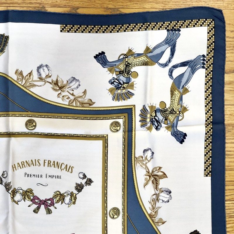 "A lovely, pre-loved Vintage HERMES Scarf<br /> Design: Premier Empire, Harnais Francais<br /> Colors: Blue, Browns, Cream, Gold, Rose<br /> Size: 45"" x 45"" (approximate dimensions, which will vary due to wear and cleaning)<br /> Condition: No tears. There are light, pale blue smudges/light brown spots which are pointed out in close-up photos. They are not obvious markings.<br /> This is a pre-loved scarf, sold in ""AS IS"" condition. Please see the last pictures for examples of the light smudges/spots."