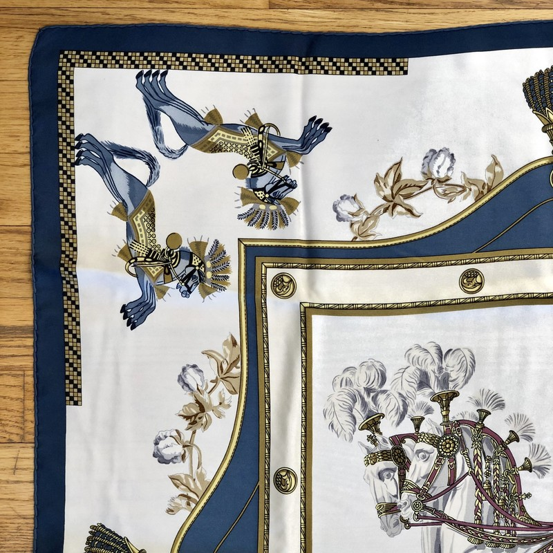 A lovely, pre-loved Vintage HERMES Scarf<br /> Design: Premier Empire, Harnais Francais<br /> Colors: Blue, Browns, Cream, Gold, Rose<br /> Size: 45&quot; x 45&quot; (approximate dimensions, which will vary due to wear and cleaning)<br /> Condition: No tears. There are light, pale blue smudges/light brown spots which are pointed out in close-up photos. They are not obvious markings.<br /> This is a pre-loved scarf, sold in &quot;AS IS&quot; condition. Please see the last pictures for examples of the light smudges/spots.