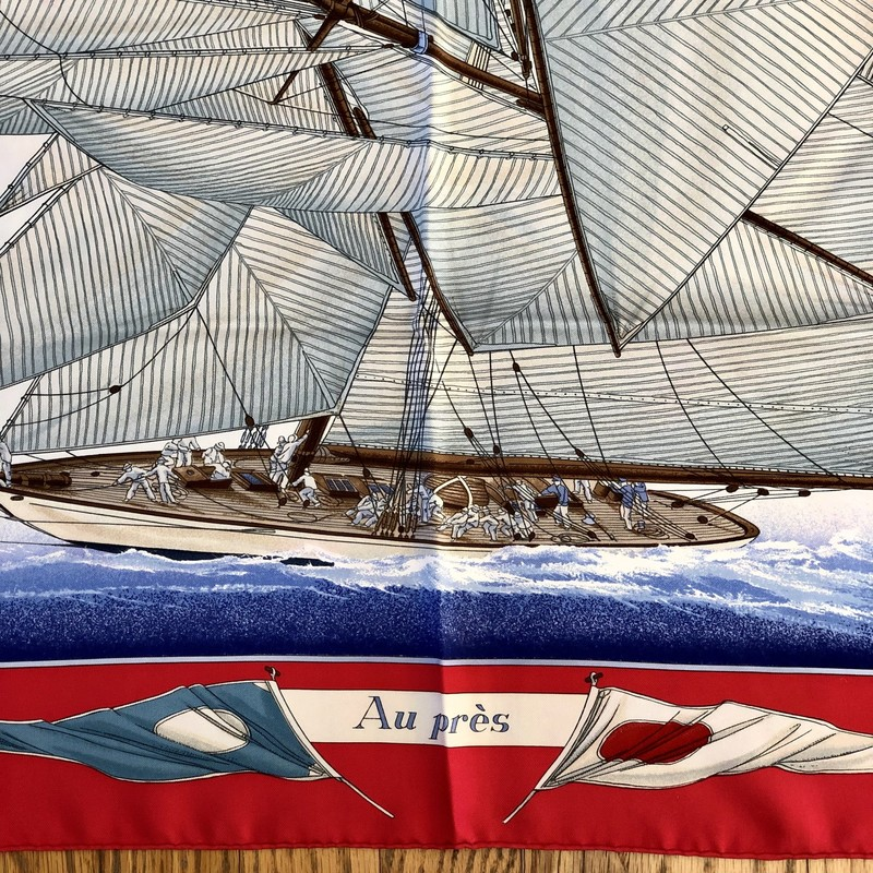"A lovely, pre-loved Vintage HERMES Scarf<br /> Design: Vent Portant, Sailboats and Nautical Flags<br /> Colors: Red, Blues, Cream, Browns, Yellow<br /> Size: 45"" x 45"" (approximate dimensions, which will vary due to wear and cleaning)<br /> Condition: No tears. There are rose-colored smudges from the red color dye.<br /> This is a pre-loved scarf, sold in ""AS IS"" condition. Please see the last pictures for examples of the smudges."