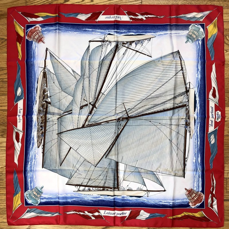 A lovely, pre-loved Vintage HERMES Scarf<br /> Design: Vent Portant, Sailboats and Nautical Flags<br /> Colors: Red, Blues, Cream, Browns, Yellow<br /> Size: 45&quot; x 45&quot; (approximate dimensions, which will vary due to wear and cleaning)<br /> Condition: No tears. There are rose-colored smudges from the red color dye.<br /> This is a pre-loved scarf, sold in &quot;AS IS&quot; condition. Please see the last pictures for examples of the smudges.