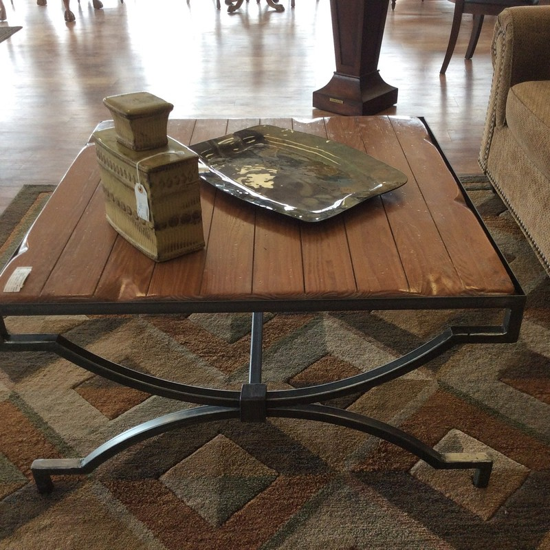 This rustic coffee table is a 38 inch square, and stands 21 inches tall. The iron base and frame have a gunmetal gray finish. The top is a solid piece of hardwood, with a maple finish and carved grooves that make it look like planks.