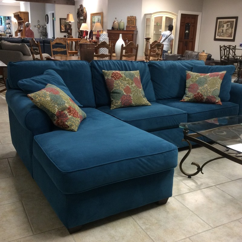 This is a great L-shaped sofa! Smaller in scale than most it would make it the perfect piece for a smaller living area or perhaps a game room, anywhere really. Still, it seats 2 comfortably with a chaise on one end. It has been upholstered in a bold, vibrant dark teal. Pillows included. Won't last long so come by soon and take a look!