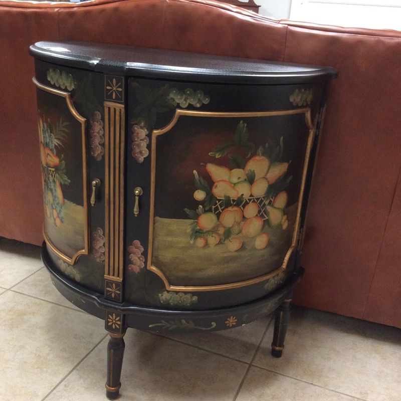 This half moon table conceals a 2-tier shelf behind a set of  beautifully painted doors. The black backdrop with a  gilded trim brings to life a colorful array of fruits and florals. This little table actually provides quite alot of storage space.