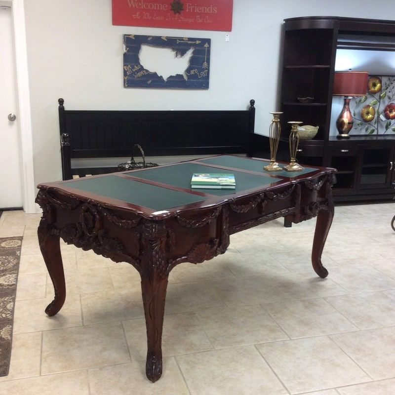 This desk is a statement piece to be sure! It is large in scale with intricately carved woodworking throughout. It features 5 drawers with dovetailing  and has a green leather inlay on the desktop.