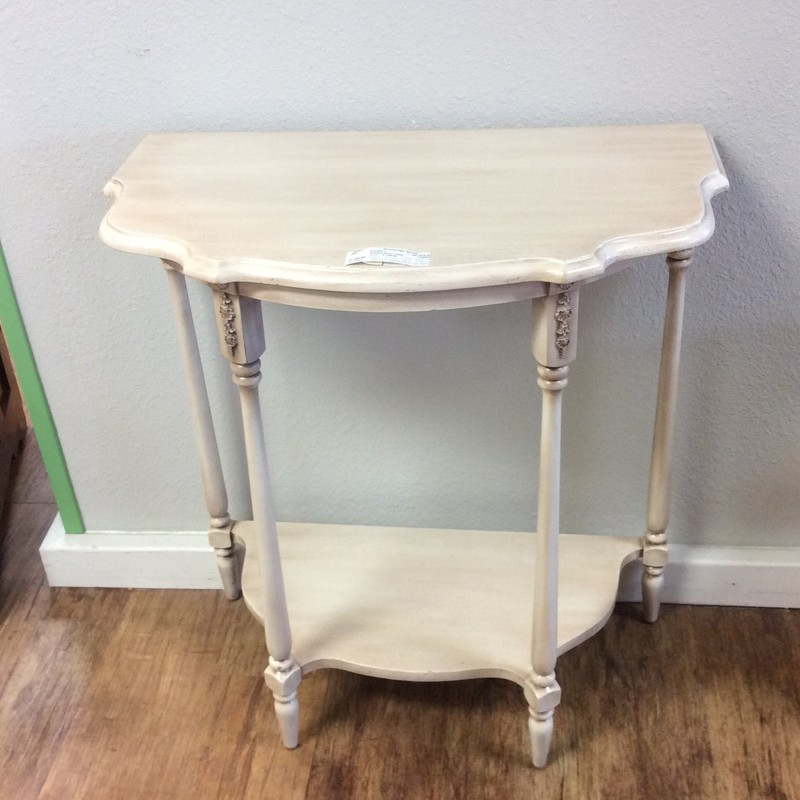 The pro who painted this piece did a fabulous job. It is a solid wood table with an antiqued white, painted finish. There is also a lower shelf and all 4 legs have pretty carved details at the tops.