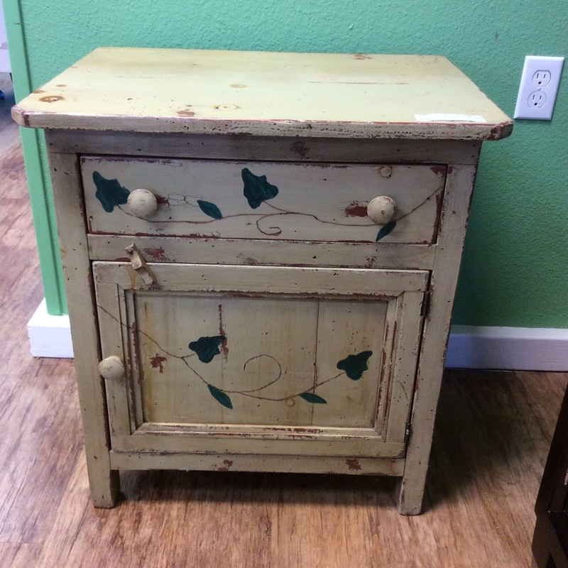 This is just adorable! We believe it is a vintage piece and it has a cute painted ivy pattern on it. There is both an upper drawer and a roomy lower cabinet, that has a turn latch.