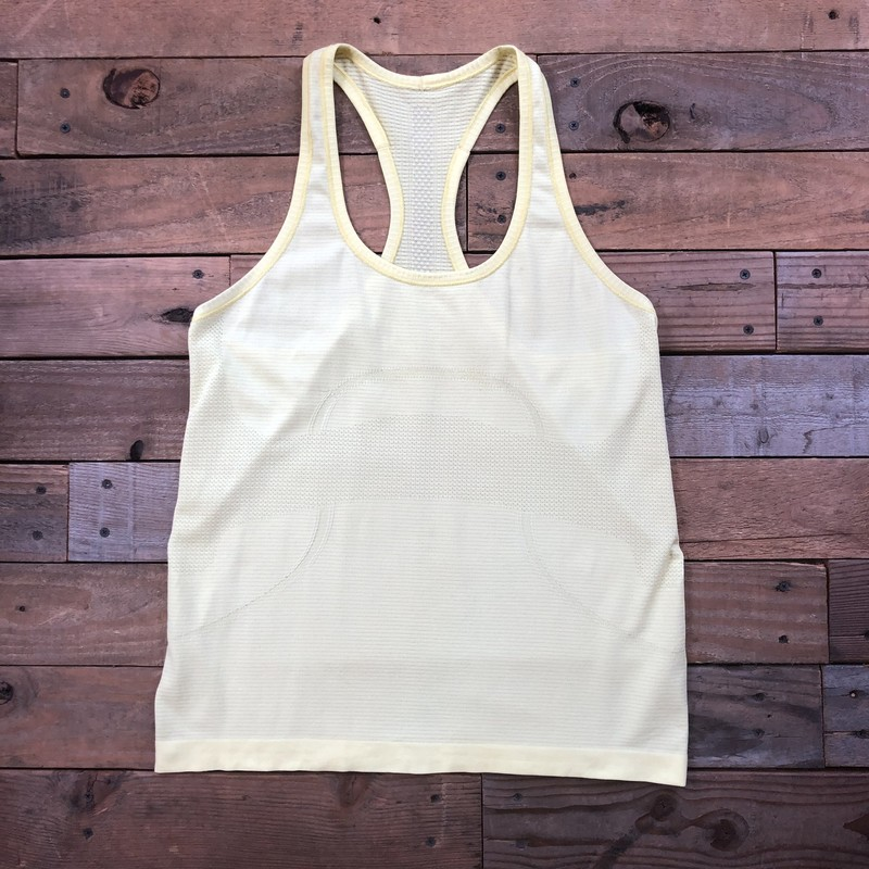 "Lululemon Racer Back Workout Tank Top<br /> Color: Yellow<br /> Size: 10<br /> Material: N/A<br /> <br /> Approximate Measurements:<br /> Shoulder-to-Shoulder: 10"" (sleeveless)<br /> Underarm-to-Underarm: 18.5""<br /> Across Bottom: 18.5""<br /> Sleeve Length: N/A<br /> Length (Shoulder to Hem): 24""<br /> *Color is more yellow than shown in picture"