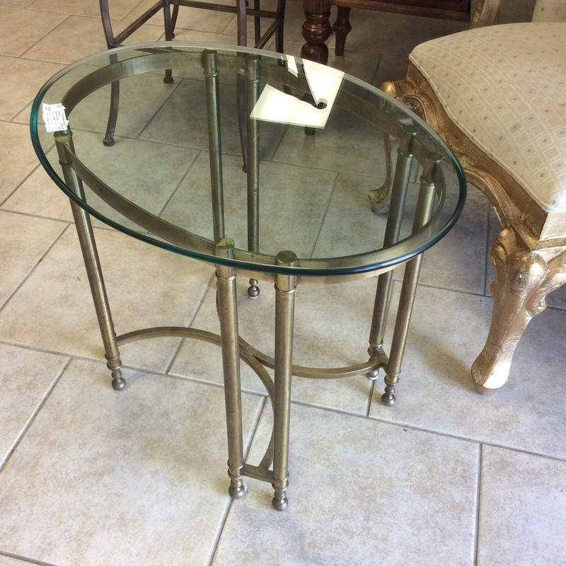 This sweet little side table is classic in design, soild and well-built. The table top is oval and sits atop a brass base.