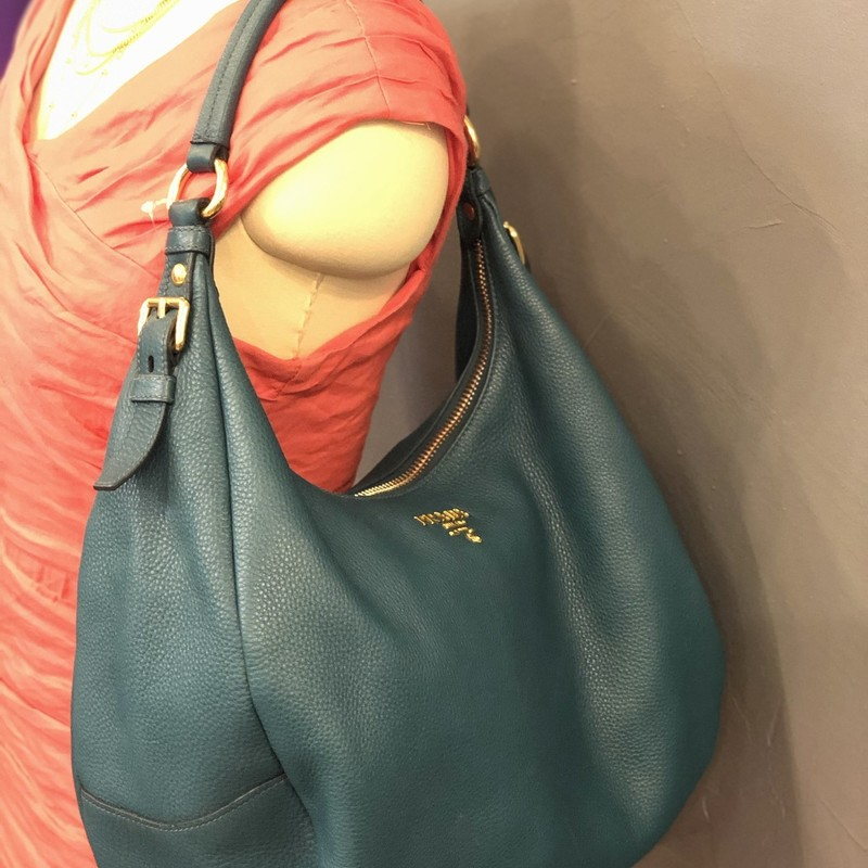 Prada Vitello Diano Hobo, Teal, Size: M<br /> <br /> Condition: GOOD. Very slight scuffing on bottom edges<br /> <br /> 13&quot;W x 10&quot;H x 5&quot;D<br /> 8&quot; strap drop<br /> <br /> We guarantee the authenticity of every bag on our site. Each bag comes with either an original sales receipt or a Certificate of Authenticity from AuthenticateFirst.com. Established in 2013, AuthenticateFirst.com<br /> (http://authenticatefirst.com) is one of the premier authentication services in the US, providing authentications of designer handbags, wallets, small leather goods, footwear, jewelry, and accessories. They employee in-house experts who have decades of experience working with hundreds of luxury brands.