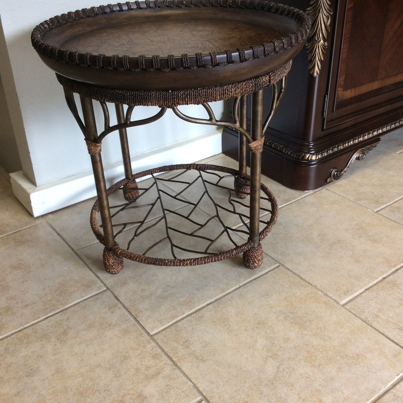 Wow, this is a stunning little table! It features a wraught iron base that has an antiqued bronzy finish, braided rope wrapped embellishments, and a solid wood top with a leather looking pattern on it. Gorgeous!