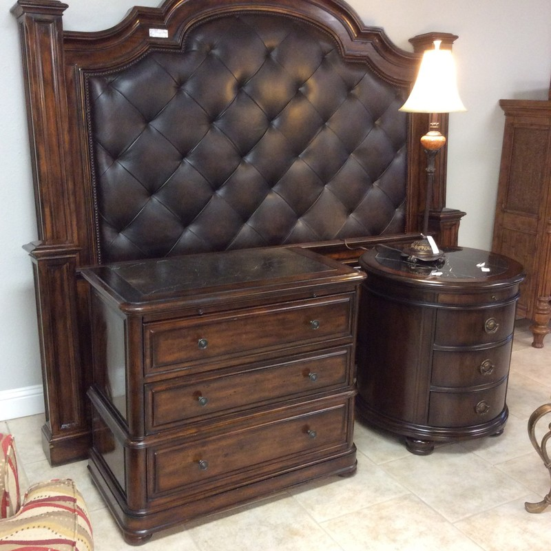 This bedroom set by Bernhardt is an eye-catcher! The set includes a king-sized headboard, footboard, a bachelors chest and a round nightstand The headboard is tufted in a dark brown leather and the frame has a slighltly weathered and distressed look. The bachelors chest includes 3 drawers with a marble top. The round nightstand also includes 3 drawers, a pull out tray and has a marble top. The entire set is in very good condition, it just needs a large room!