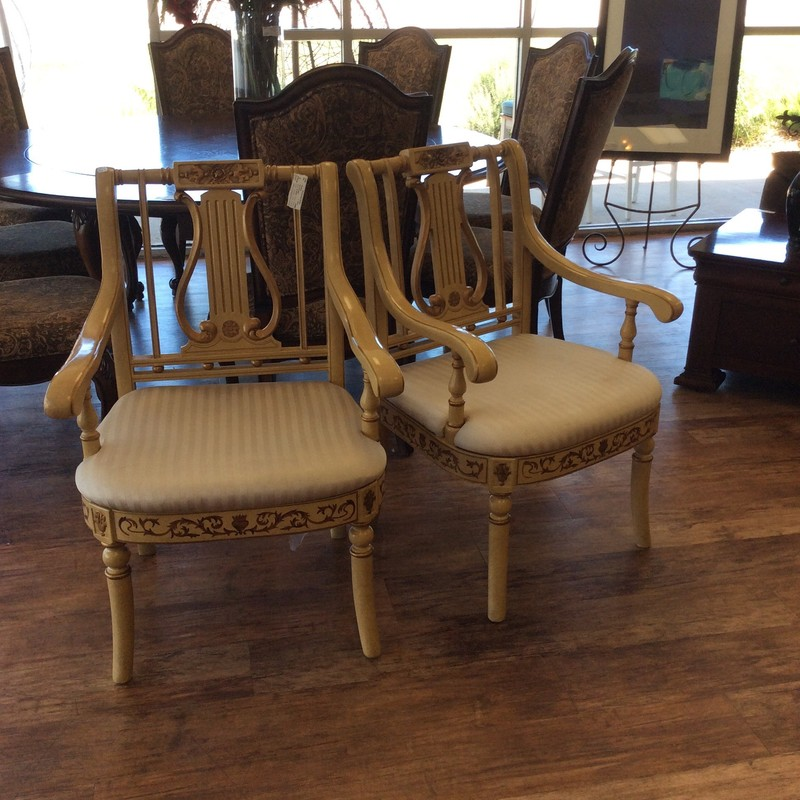 This charming pair is full of personality! The wood frame has been painted and includes detailed woodwork from top to bottom. The chair seat has been upholstered in an elegant champagne colored striped fabric. Check out the back of the chair too, it's just as cool!