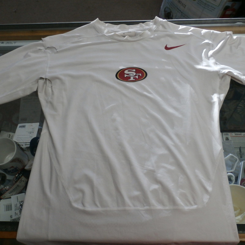 "Nike Men's San Francisco 49ER's Compression shirt size XL white #31233<br /> Rating:   (see below) 4- Fair Condition<br /> Team: San Francisco 49ER's<br /> Player:  Team<br /> Brand: Nike<br /> Size: Men's   XL(Measured Flat: across waist 19"", length 29"" )<br /> Measured flat: armpit to armpit; top of shoulder to the bottom hem<br /> Color: white<br /> Style: short sleeve; screen pressed ; compression shirt;<br /> Material:   91% polyester 9% spandex<br /> Condition: - 4- Fair Condition - wrinkled; minor pilling and fuzz; there are 4 tears or hole on the right sleeve and one in the center of the back; some discoloration;<br /> Item #: 31233<br /> Shipping: FREE"