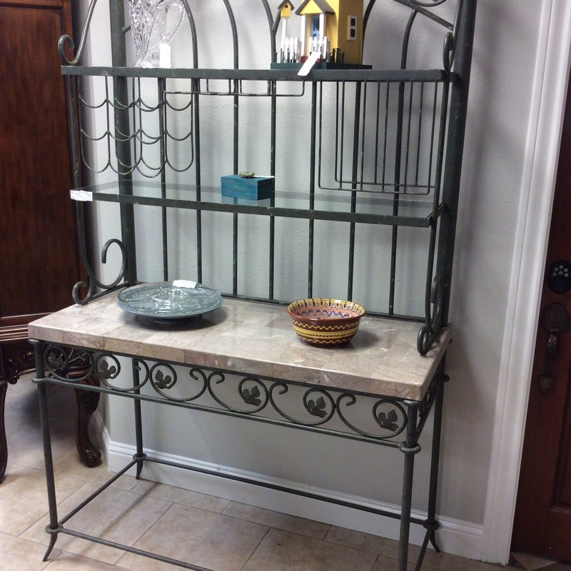 BARGAIN ALERT!!! This attractive piece is priced to move. It features a heavy iron frame with leaf decorations. Up top, there are 2 glass shelves, a 9 bottle wine rack, 3 stemware slots, and a plate rack. The center shelf is wood covered in a patchwork of pretty marble tiles