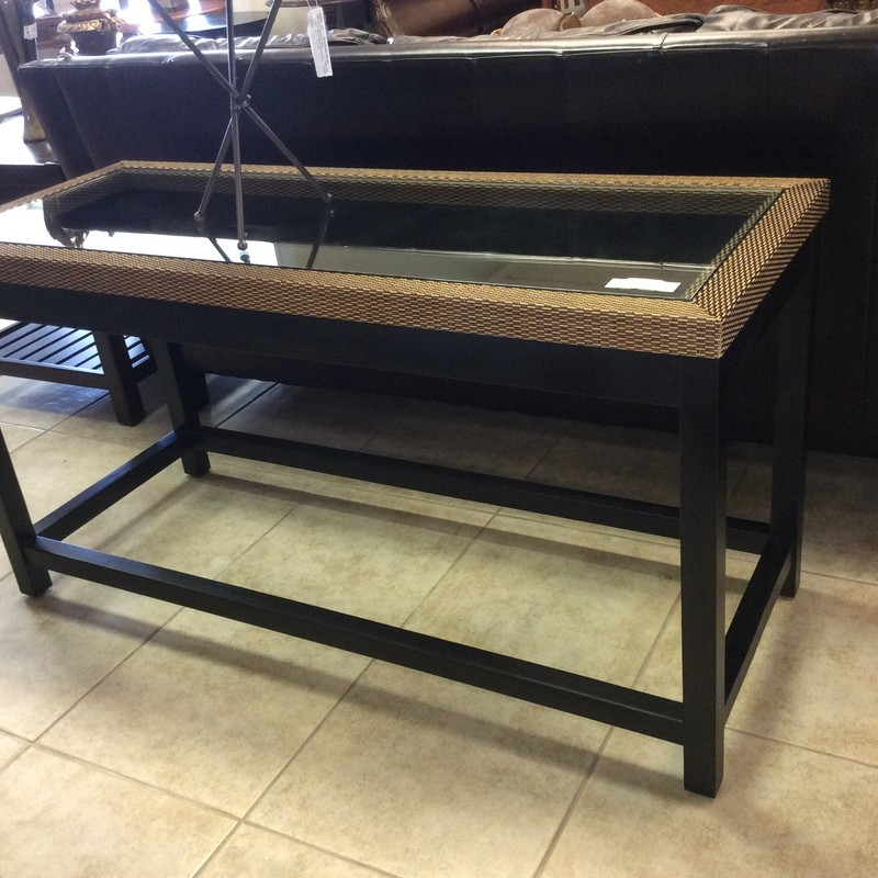 This pretty sofa table is in great condition. It features a wood frame with a painted matte black finish with a woven wicker edge around the top. The piece of glass that fits into the glass is a full 1/2 inch thick, and is quite heavy.