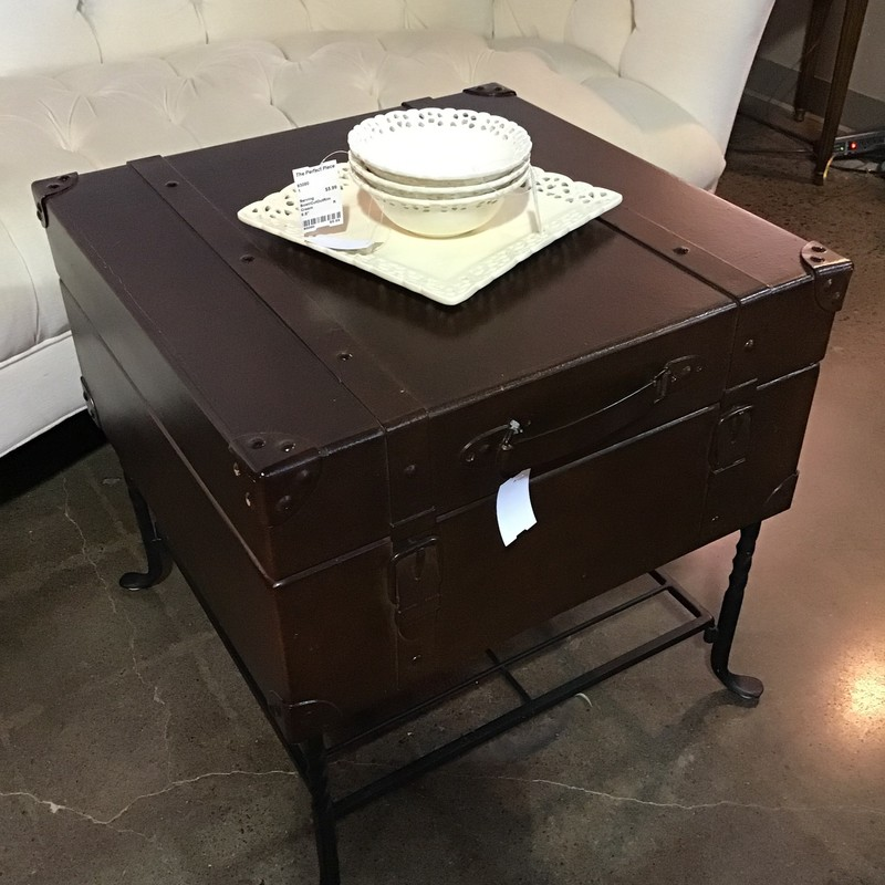 With its spacious storage compartment, this Square Storage Trunk Accent Table is not only beautiful but functional as well. The table is dark brown sitting on top of black wrought iron legs with a lower shelf for additional storage.  Two faux buckles on the front of this table bring an added element of design.<br /> <br /> Dimensions:  22x22x22