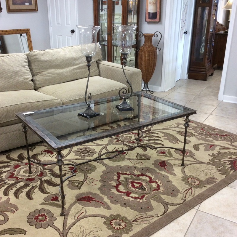 This simple, yet elegant, coffee table features a sculpted iron base with an antiqued pewter finish. The glass topper sits down firmly into the iron frame. It is a bit taller than most coffee tables, standing at 21 inches tall.