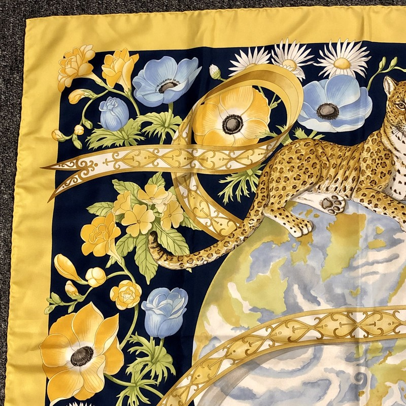 "Ferragamo 100% Silk Scarf. Spectacular Mint Condition.<br /> Pre-loved, made in Italy<br /> Design: Leopard sitting on the earth, Floral, Bird<br /> Size: 34"" X 34""<br /> Colors: Yellow, Blues, Greens, White, Browns"