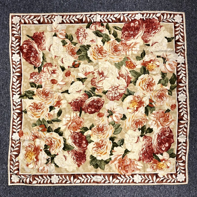 "Gucci Silk Scarf, hand-rolled excellence! Exquisite and in mint condition. Pre-loved.<br /> Material: 100% Silk, Made in Italy<br /> Floral design<br /> Colors: browns, greens, reds, yellow<br /> Size: 33"" x 34""<br /> Dry clean only"